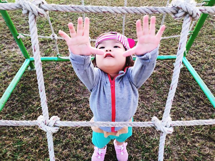 Clutch Capture Tomorrow Child Childhood Playing Happiness Fun Enjoyment Front View Playground Outdoor Play Equipment Casual Clothing Jungle Gym Babyhood Monkey Bars One Baby Girl Only Baby Carriage Arms Raised Arms Outstretched Slide - Play Equipment