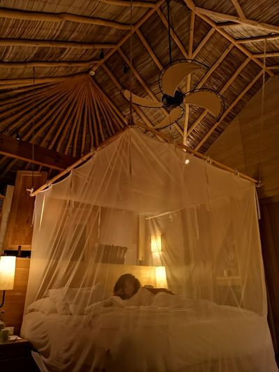 Woman lying in four poster bed at hotel