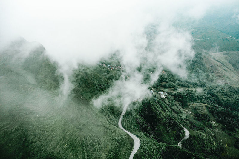 Scenic view of fog on mountain against sky