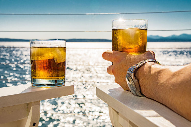 Cropped image of man holding rum glass at beach