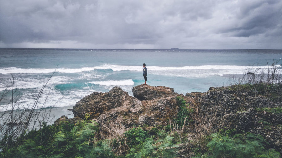 Man standing on rock by sea against cloudy sky