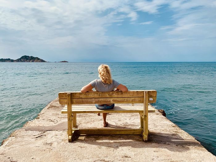 Rear view of woman sitting on bench by sea against sky