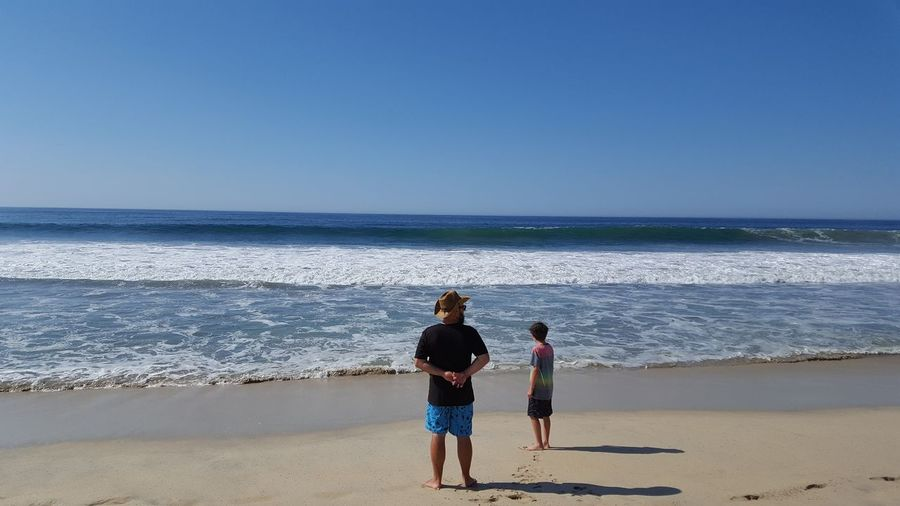Father and son standing on sea shore at beach against clear blue sky