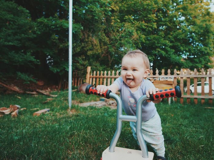 Cheerful little baby with walker on lawn