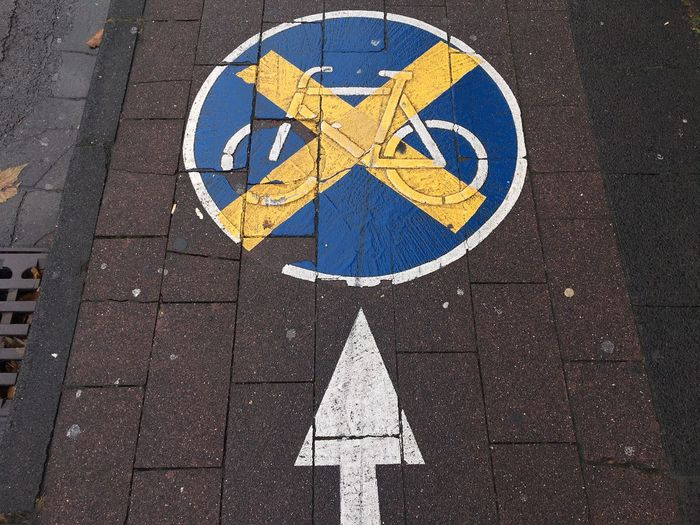 High Angle View Of Arrow Symbol With Bicycle Lane On Footpath