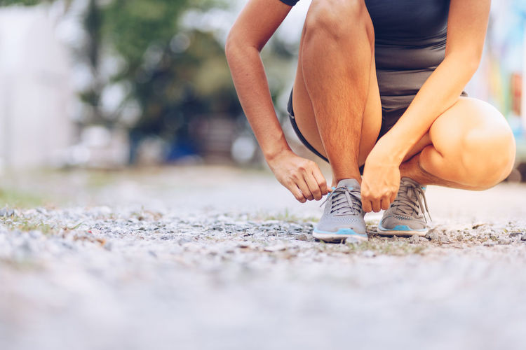 Low section of athlete tying shoelace on street