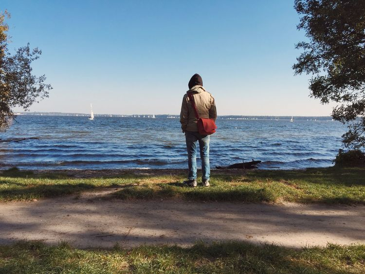 Teenager from behind looking at lake and boats in sunny autumn weather Anonymous Autumn Behind Boats Boy Fall Horizon Lake Man One People Person Sailing Sky Teenager