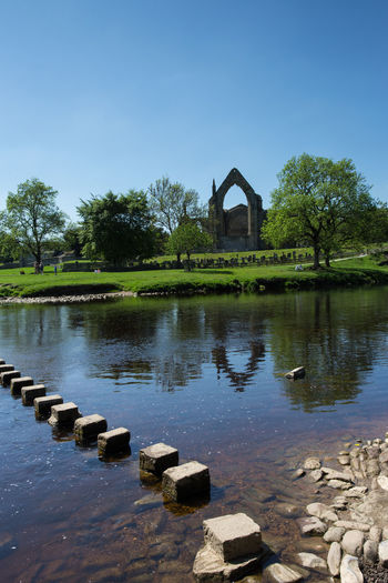 Stepping stones across the River Wharfe at Bolton Abbey, North Yorkshire, England, UK. Abbey Bolton Abbey Copy Space River Wharfe Architecture Beach Building Building Exterior Built Structure Clear Sky Day Nature No Clouds Outdoors Reflection River Ruin Sky Stepping Stones Tranquility Tree Water