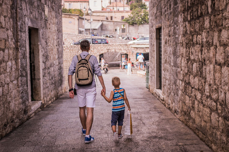 Rear View Of Father Holding Hands Of Son While Walking In Alley Amidst Buildings