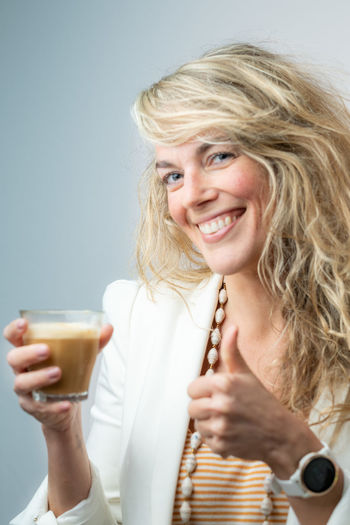 Portrait of a smiling young woman drinking glass