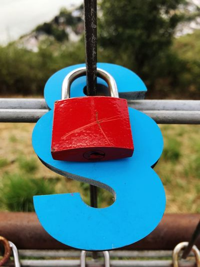 Law Section Paragraph Paragraph Sign Lock Hanging Red Day Close-up Blue Metal Focus On Foreground Protection Padlock Security Safety Outdoors Nature