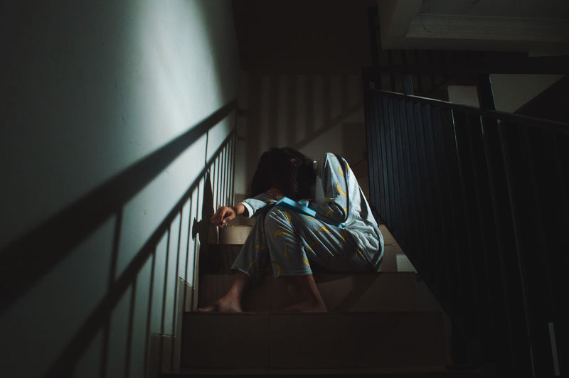 Mood Moody Cinematic My Best Photo People Real People One Person Indoors  Wall - Building Feature Railing Staircase Window Lifestyles Building Steps And Staircases Day Casual Clothing Sitting Women Depression - Sadness Emotion Sad Sadness Sad & Lonely Woman Dark Night