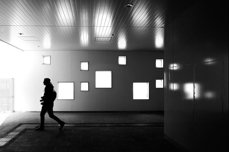 Full length of silhouette woman walking in illuminated corridor