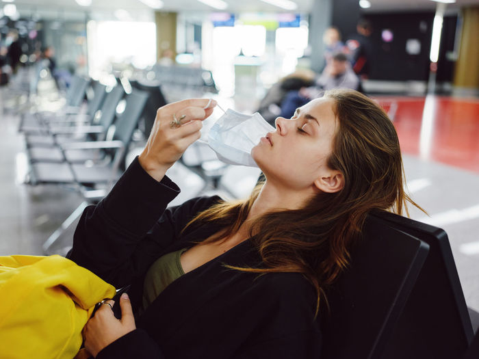 Woman removing mask while sitting at airport