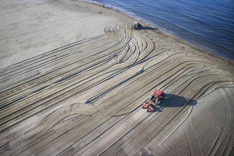 High angle view of tractors on sand at beach
