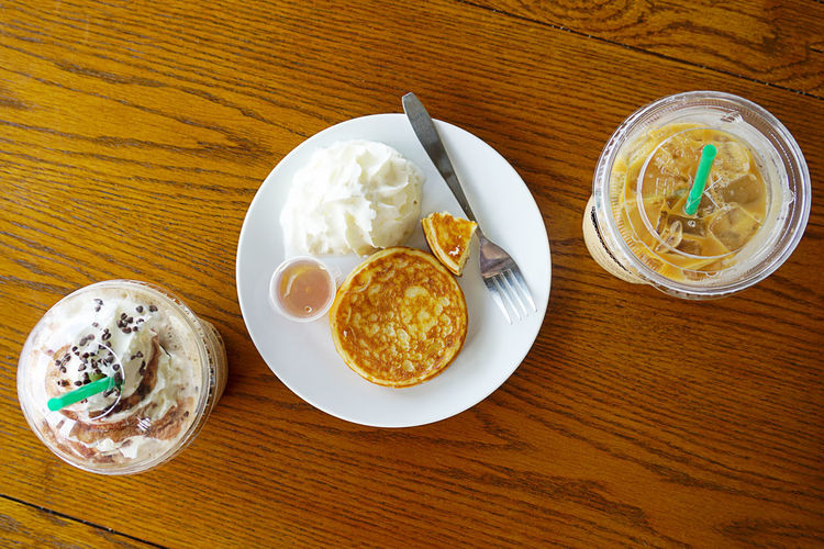 Coffee break at Starbucks new coffee shop drive thru,Chon buri Thailand. Coffee Break Starbucks Pancakes Whipped Cream Cream On Table Flat Lay Food Top View Latte Ice Coffee Coffee Cup Coffee Time Thailand Fork Table Food And Drink Freshness Still Life Ready-to-eat Wood - Material Indoors  Plate Directly Above Bowl Glass High Angle View Drinking Glass No People Healthy Eating Drink Serving Size Wellbeing Breakfast