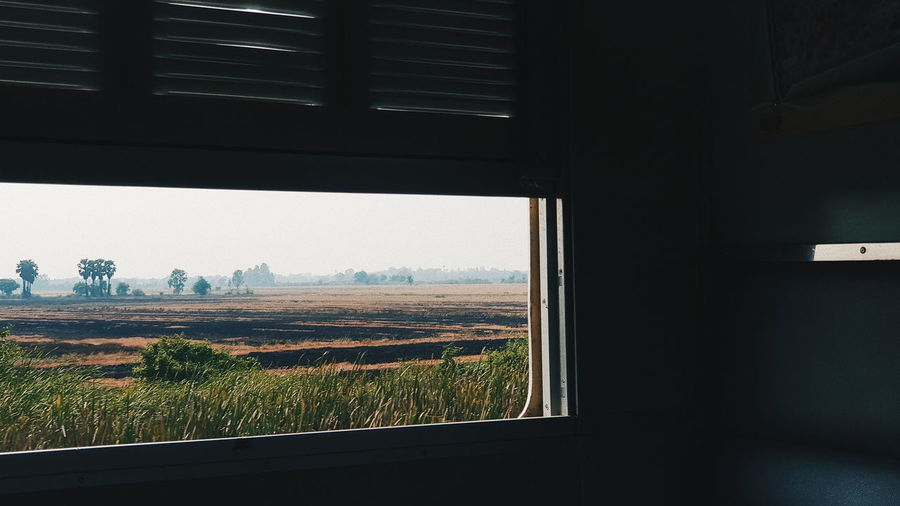 Window Indoors  Plant Landscape No People Glass - Material Transparent Tree Day Field Environment Nature Land Sky Architecture Beauty In Nature Growth Scenics - Nature Train