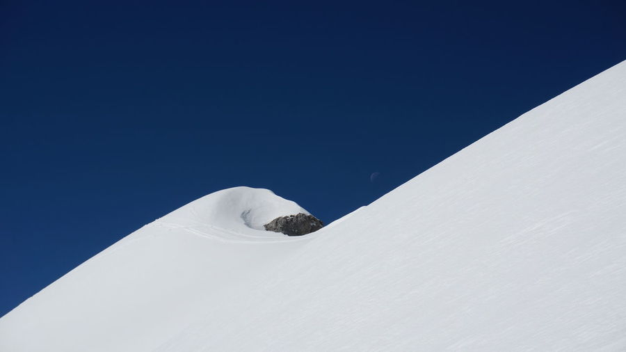Low angle view of snow mountain against clear blue sky