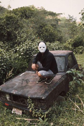 Man Sitting On Old Vehicle