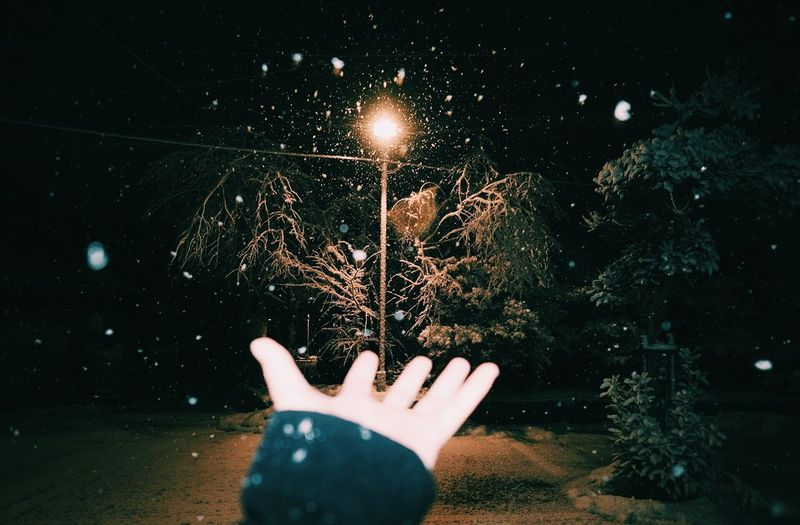 Human Hand Night Human Body Part Human Finger One Person Real People Illuminated Cold Temperature Snow Winter Outdoors Nature Close-up Lifestyles Star - Space People Tree Snowflake Space Astronomy