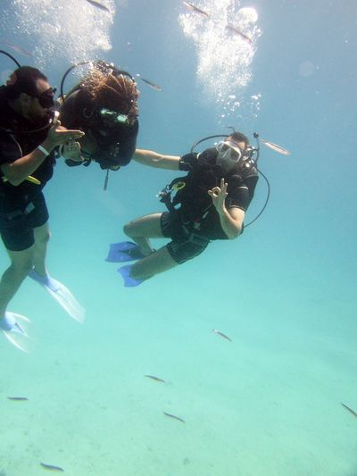 Friends Gesturing While Scuba Diving Undersea