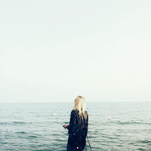 Scenic View Of Woman At Sea Against Blue Sky