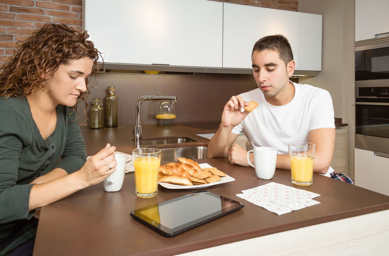 Serious and bored young couple having a breakfast in the home kitchen Family Fresh Fruit Girlfriend Thirties Relaxing Husband Boyfriend 30s Wife Relationship Adult Lifestyle Interior Love Cup Caucasian Healthy Two Coffee Glass Orange Girl Juice Meal Drink Together Young Woman Kitchen Man Indoors  Food Morning Technology Newspaper Digital Tablet News Read Problems Bored Serious Male Home People Female Couple Breakfast