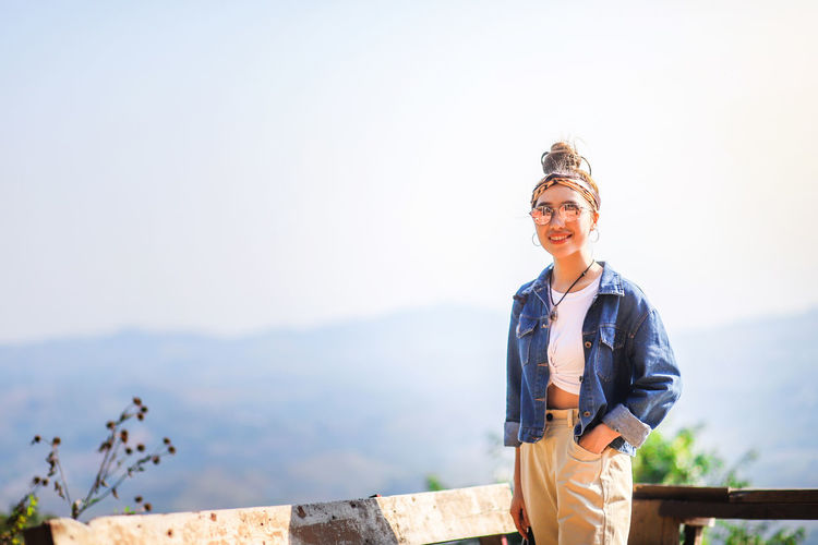 Portrait of smiling young woman standing at observation point against sky