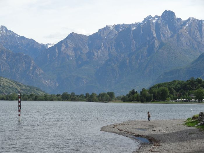 Woman standing on field by lake against mountains