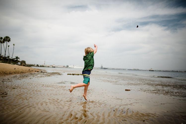 Full length of boy running on beach