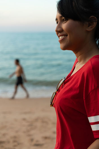 Beach Land Sea Water Real People Focus On Foreground Young Adult Smiling Side View Happiness Standing Emotion Outdoors Passerby Walker Sand Shore Smile Happy Sunglasses Torso Chest Girl Asian  Red Shirt