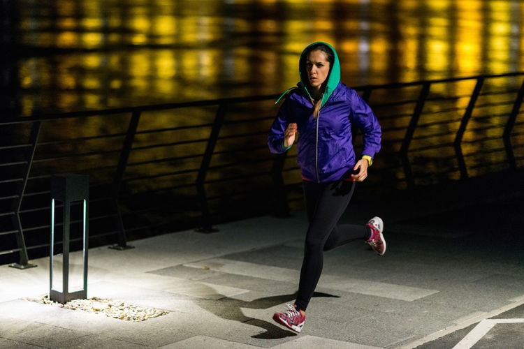 Full Length Of Woman Running On Footpath At Night