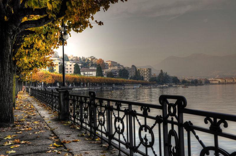 Sidewalk by river against sky