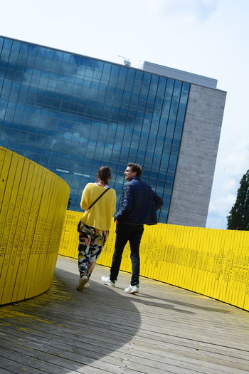 Adult Architecture Building Exterior Built Structure City Couple - Relationship Coworker Day Full Length Males  Men Modern Office Building Exterior Outdoors People Sky Standing Togetherness Two People Walking Yellow Young Adult International Women's Day 2019