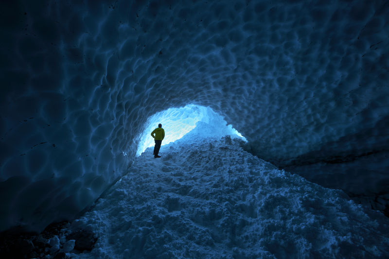 Rear view of man standing in snowy cave