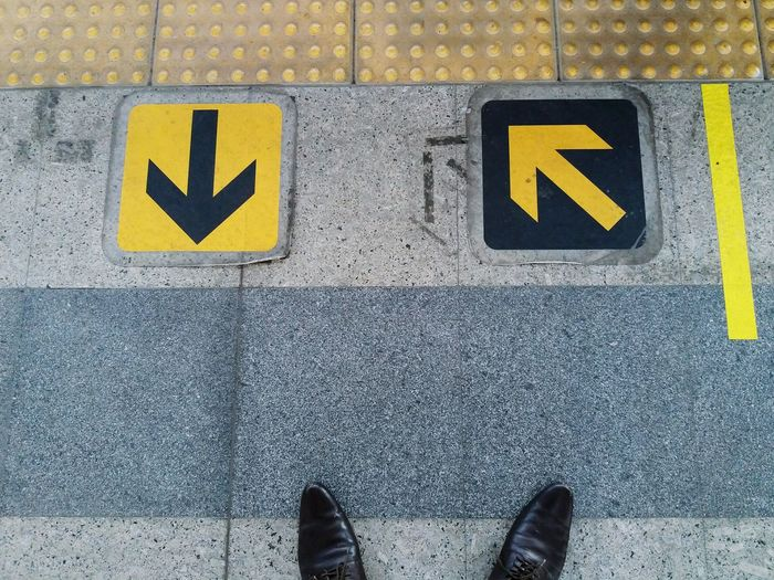 Low Section Of Man Standing By Arrow Symbols On Footpath