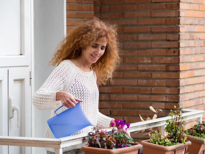 Young woman smiling while holding plant against brick wall