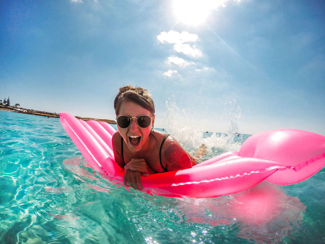 Cyprus Pink Day Enjoyment Fashion Floating On Water Happiness Holiday Inflatable  Leisure Activity Lens Flare Nature One Person Outdoors Pool Portrait Real People Sky Smiling Sunlight Swimming Pool Trip Vacations Water Young Adult