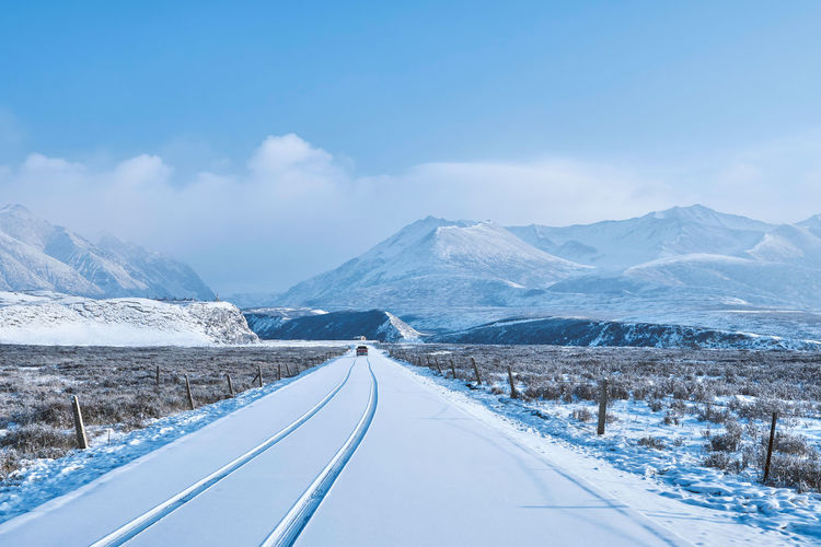 Diminishing perspective of snow covered road against sky