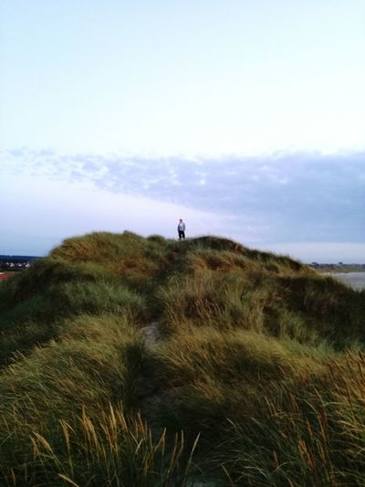 Distant view of man standing on hill against sky during sunset
