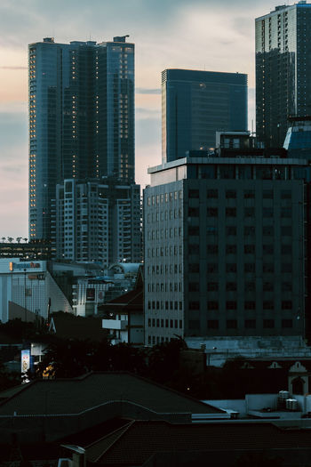 Modern buildings in city against sky at dusk