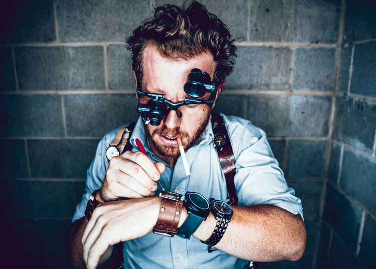 Man wearing loupe glasses repairing watch while standing against wall