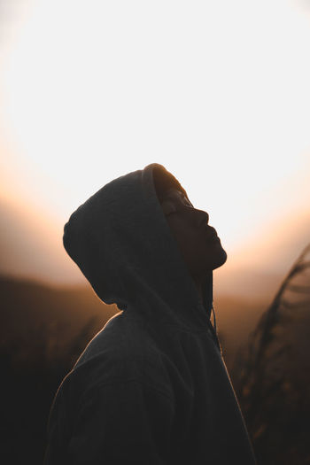 Close-up of young man wearing hoodie against sky during sunset