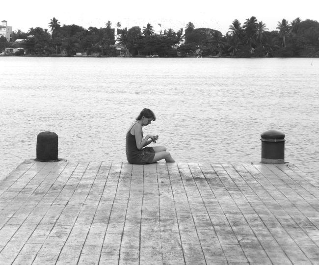 Side view of young woman sitting on lake against trees