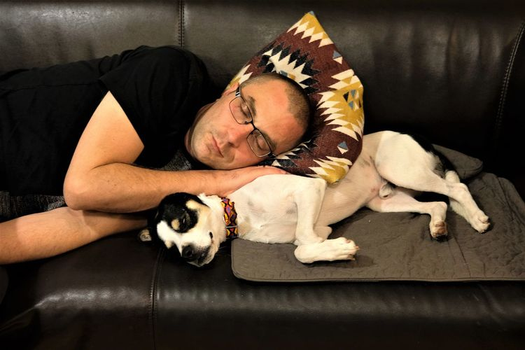 Man with dog relaxing on sofa at home