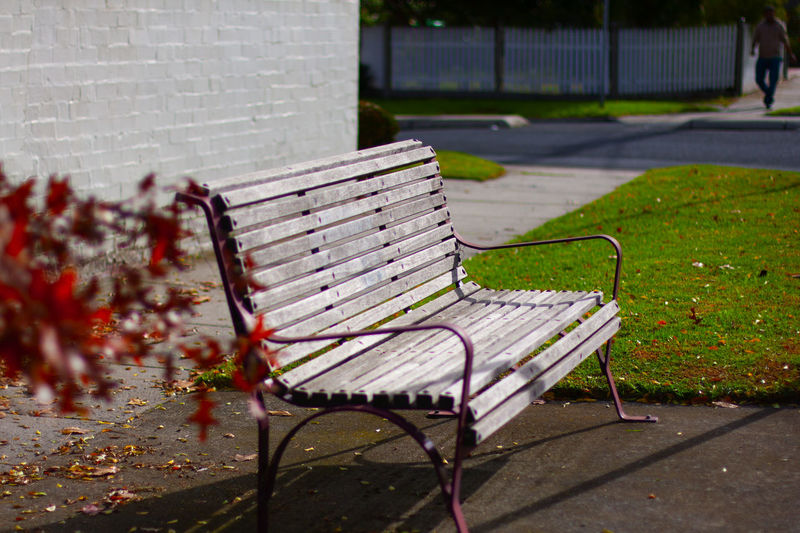 Empty bench in park against wall