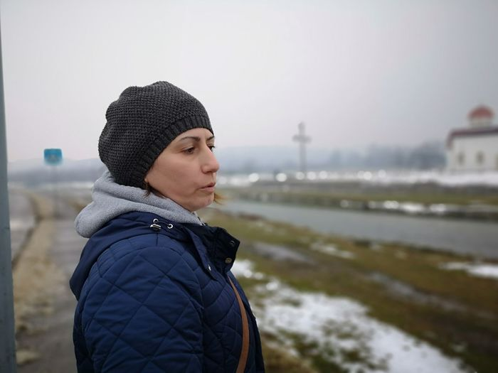 Woman looking away against sky during winter
