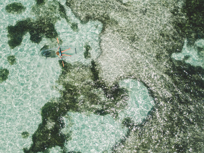 Aerial view of woman on inflatable boat in sea