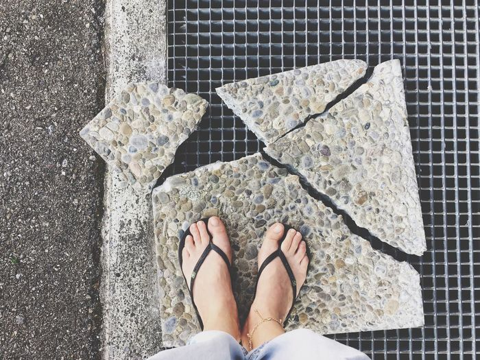 Low section of woman standing on broken stone tile over metal grate