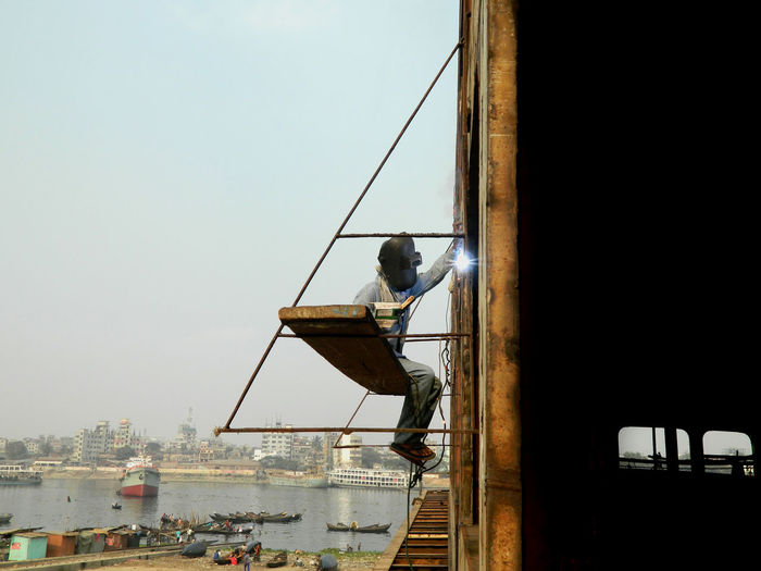 Welder working at construction site against clear sky